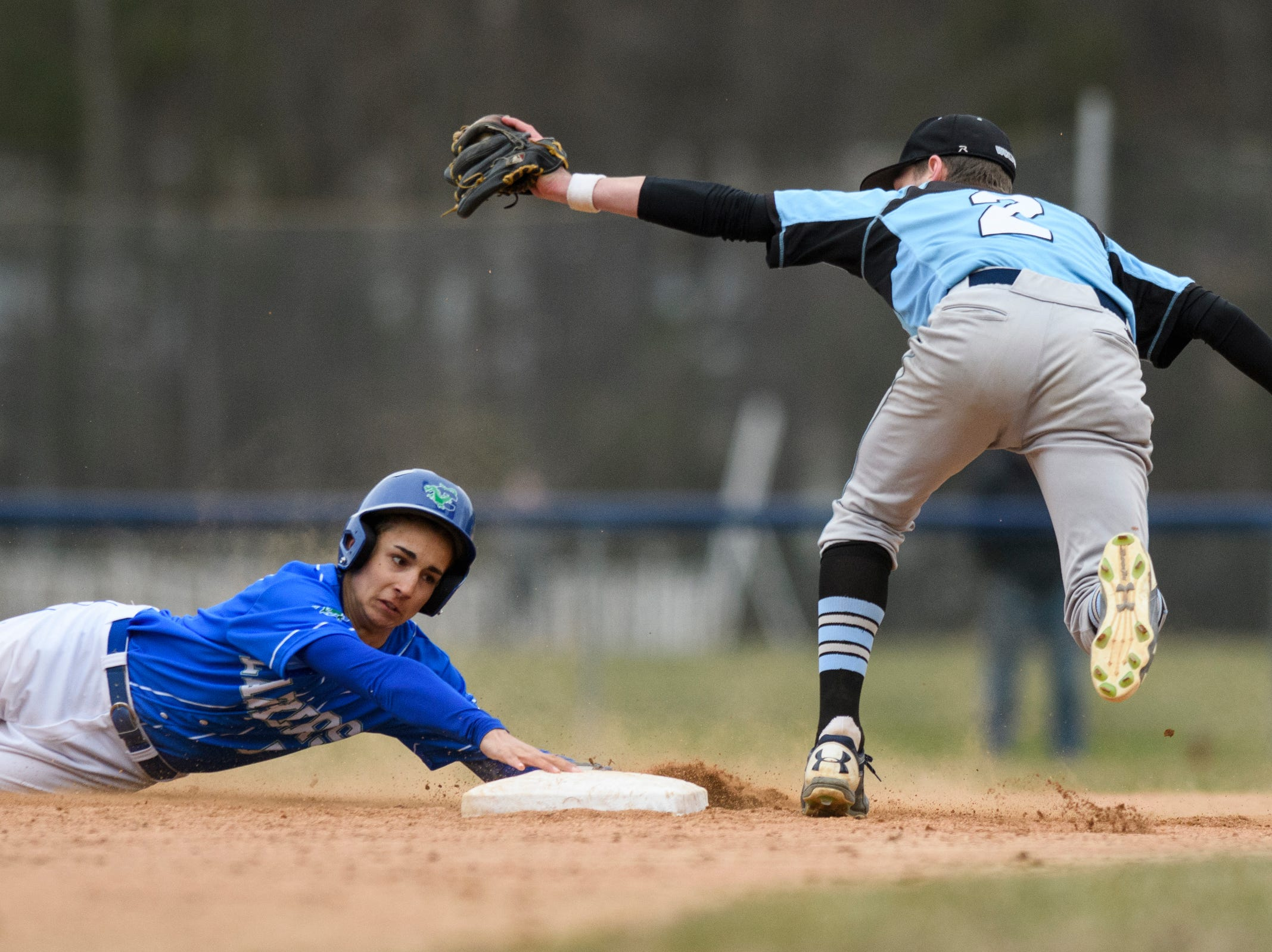 Colchester's Saul Minaya (3) slides past second base as South Burlington's Nolan Antonicci (2) trees to tag him during the boys baseball game between the South Burlington Wolves and the Colchester Lakers at Colchester high school on Thursday afternoon April 18, 2019 in Colchester, Vermont.