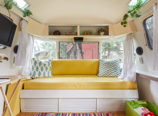 Kick back in this vintage air stream located in Austin, Texas. The unique home is stylishly decorated with retro-themed furniture and bright aesthetic colors.