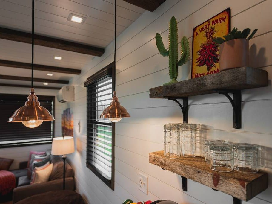 """The """"Mainsail,"""" a tiny 40-foot container home located in Waco, Texas, features modern, luxurious furniture and a rooftop deck lit by LED lights."""