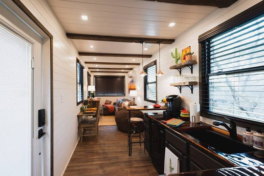 "The ""Mainsail,"" a tiny 40-foot container home located in Waco, Texas, features modern, luxurious furniture and a rooftop deck lit by LED lights."