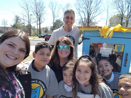 Larry Abrams, founder of BookSmiles, brings a Little Free Library to Lindenwold School No. 4. ESL teacher Nancy Bragg (in sunglasses) painted the library. Reading teacher Marie Aberant (left) said her students (from left)  Anthony Rubio-Belis, Edwynn Maldonado, Nely Betran-Salazar and Valerie Corona and Dominic Roberts were inspired to ask for a Little Free Library at the school after reading a book about the program