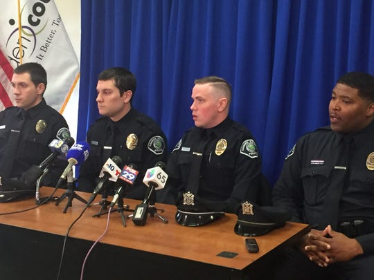 Camden County Police officers, left to right, Brian McCline, Vincent Russomanno, Joseph Mair and Vaughn Edwards, on Friday discuss their rescue of motorists from a fiery crash on I-676 in Camden.