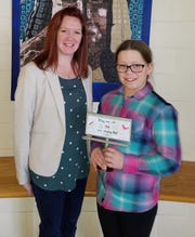 Adena Middle School student Lydia Beery holds a miniature billboard with her winning Earth Day design which was recently presented to her by Erica Tucker (left), district coordinator for the Ross, Pickaway, Highland, and Fayette Solid Waste District Coordinator.