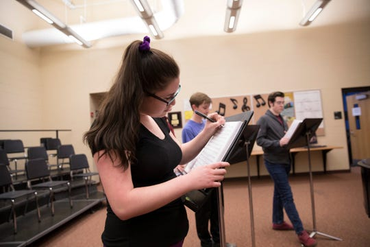 Polarity singer Kayleah Shiland makes notes on her music sheets as they prepare a new song.