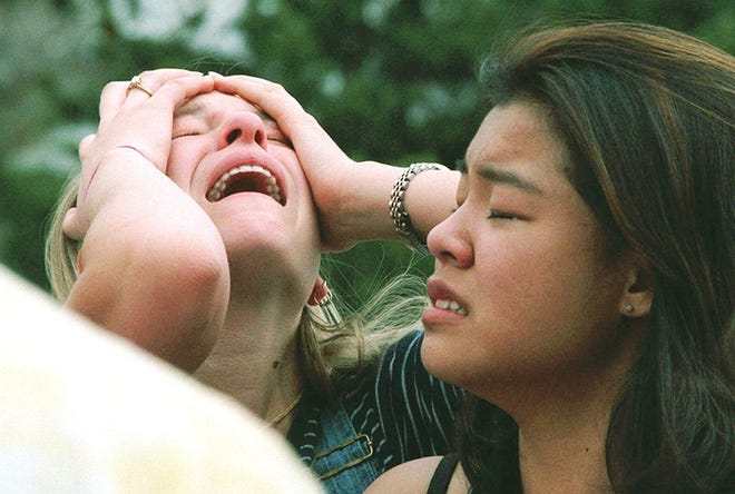 Columbine High School students react at a triage scene near the school in Littleton, Colorado, after two young men opened fire at the suburban Denver high school on April 20, 1999.