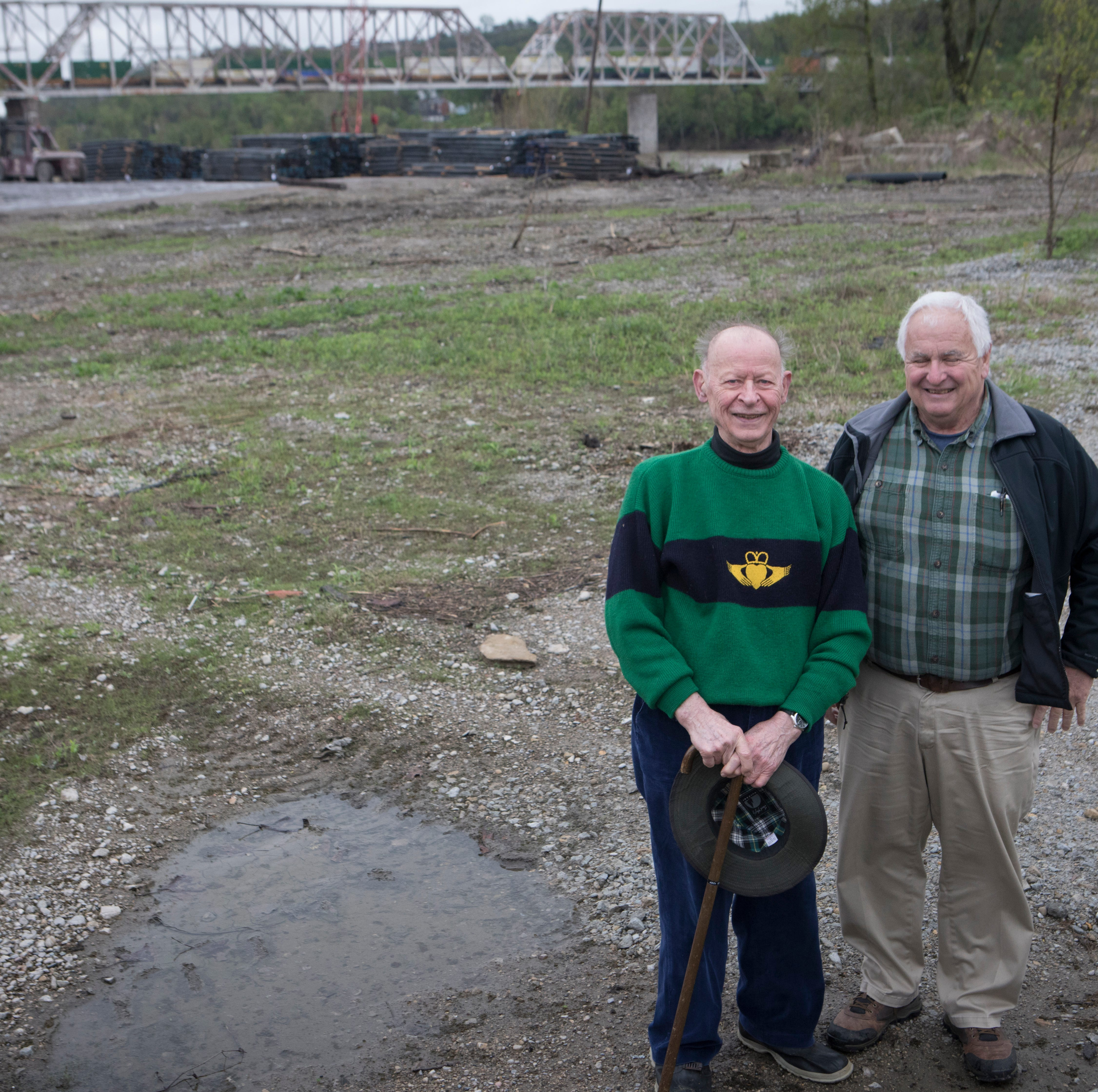 Jack Degano, left, and Gregory Lang stand on public land that is planned to be a park at Evan's Field on Friday, April 19, 2019. Behind them is a site where Hilltop Concrete is hoping to move from their location from their current location near Paul Brown Stadium.