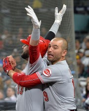 Apr 18, 2019; San Diego, CA, USA; Cincinnati Reds right fielder Jesse Winker (33) is caught by first baseman Joey Votto (19) while doing a celebratory trust fall into the dugout after hitting a solo home run in the ninth inning against the San Diego Padres at Petco Park. Mandatory Credit: Jake Roth-USA TODAY Sports