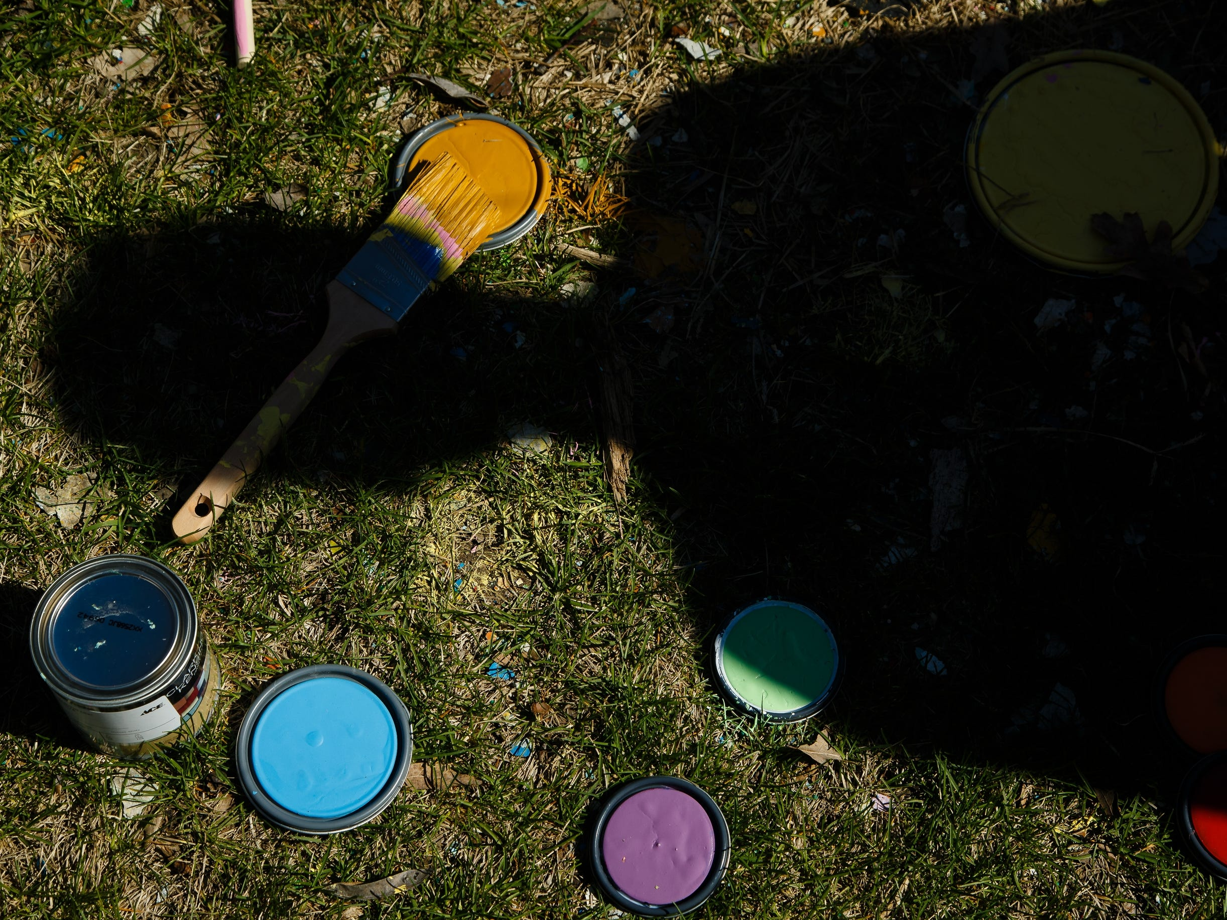 Paint lids lay on the grass as students at Drake University paint Painted street on Friday, April 19, 2019, in Des Moines.