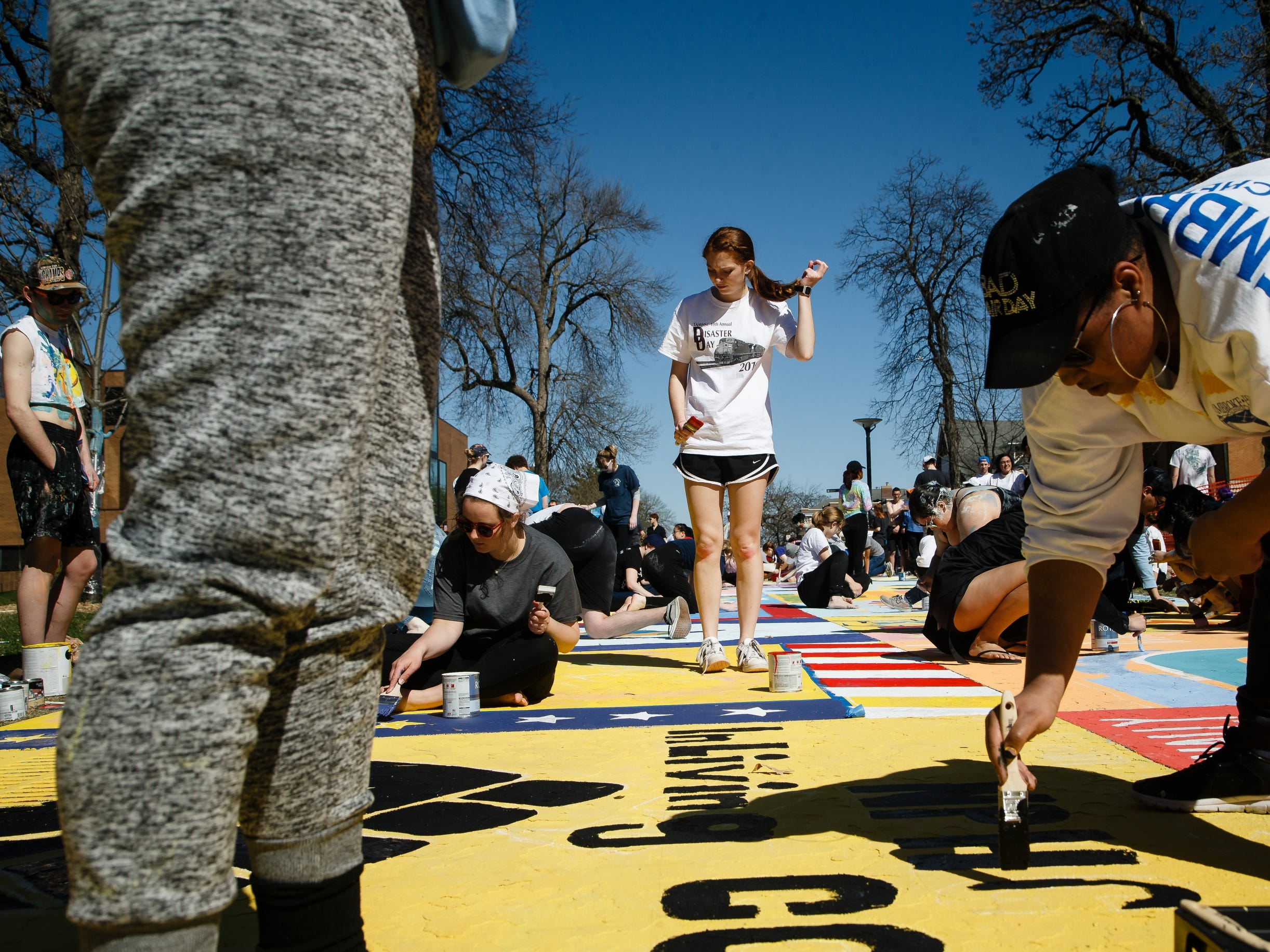 Rebecca Curry, 20 of College Station, Tex., center, joins students at Drake University painting Painted Street on Friday in Des Moines.