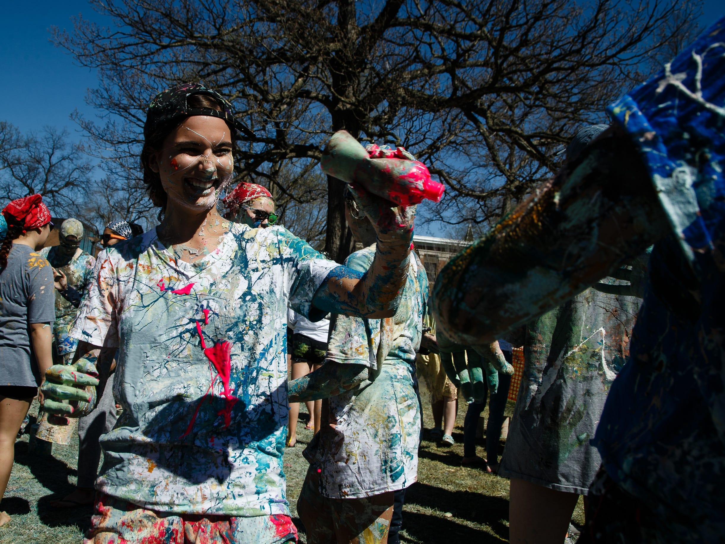 Jade Spady, 19 of Hastings, NE attempts to throw pink paint as students at Drake University paint Painted street on Friday, April 19, 2019, in Des Moines.