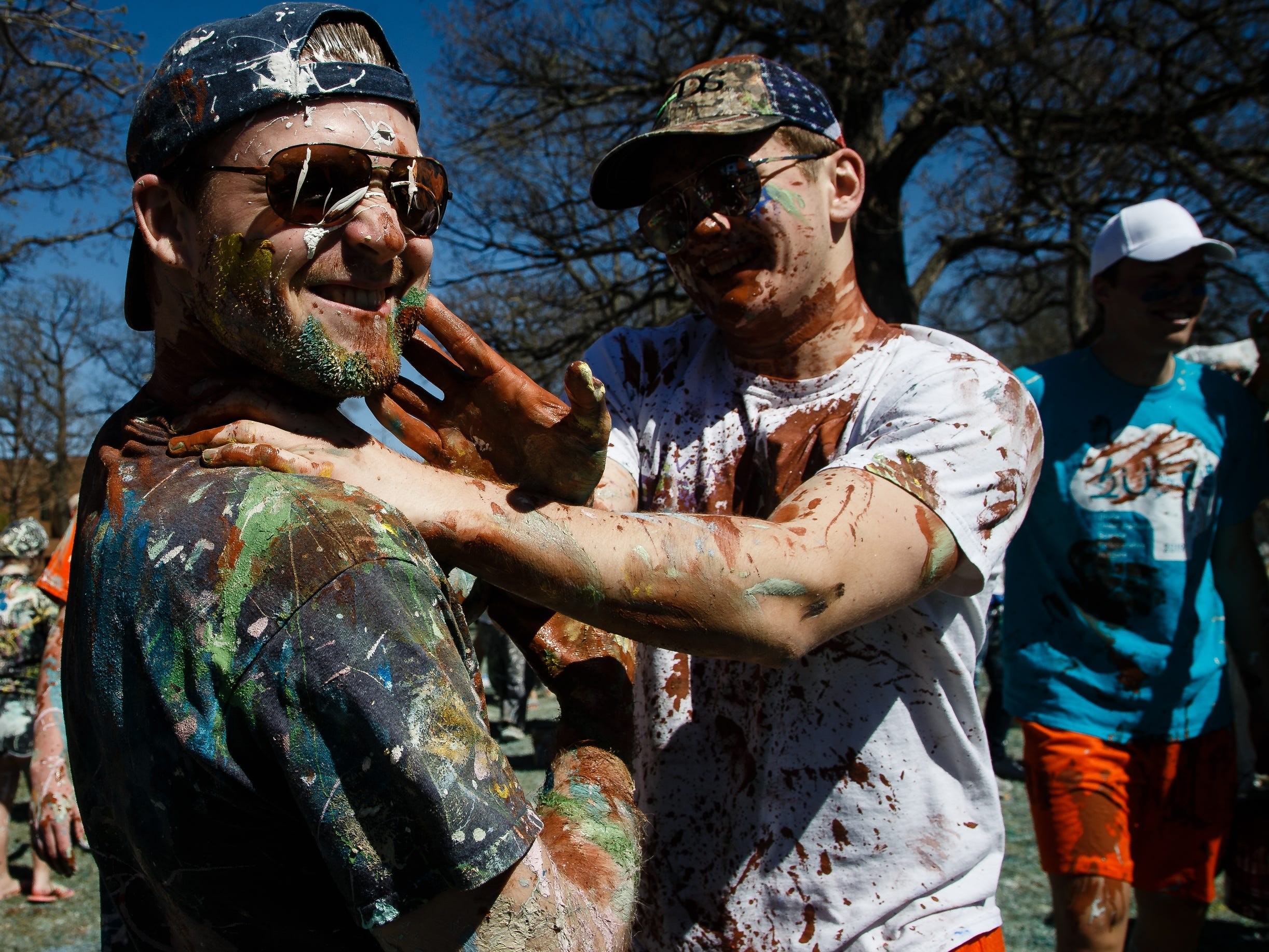 Declan Merbeth, 19 of Frankfort, Ill, right, spreads paint on Benedict Schultz, 19 of Dubuque as students at Drake University paint Painted street on Friday, April 19, 2019, in Des Moines.