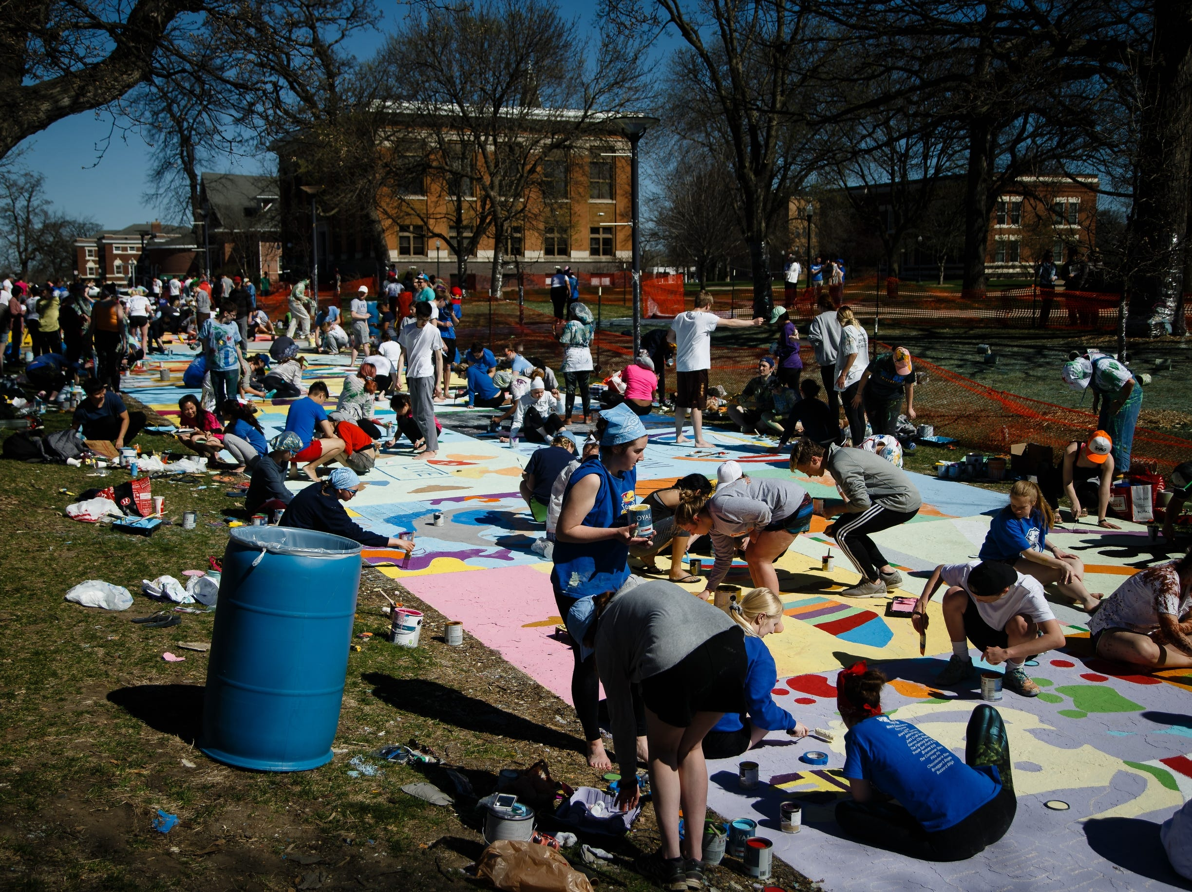 Students at Drake University paint Painted street on Friday, April 19, 2019, in Des Moines.