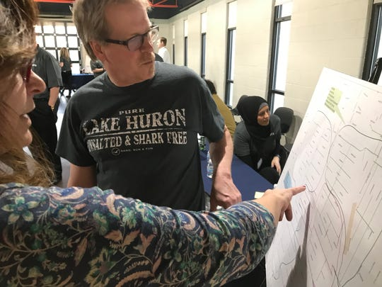 Lisa Wetzen shows her husband, Doug McElroy, the circuit that feeds their house in Pleasant Ridge at the DTE open house on Thursday, April 18, 2019. Bill Laitner/DFP