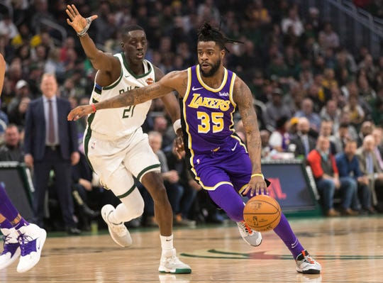 Los Angeles Lakers guard Reggie Bullock drives to the basket against Milwaukee Bucks guard Tony Snell at Fiserv Forum in Milwaukee, March 19, 2019.