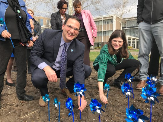 Oakland County Commissioner Dave Woodward (D-Royal Oak) plants pinwheels Thursday with U.S. Rep. Haley Stevens (D-Rochester Hills) outside the Oakland County Complex to mark April as National Child Abuse Prevention month.
