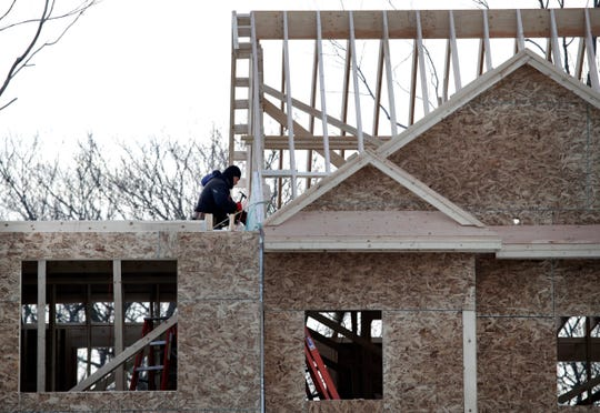 In this Jan. 23, 2019, photo, construction workers build new housing in Salisbury, Mass.