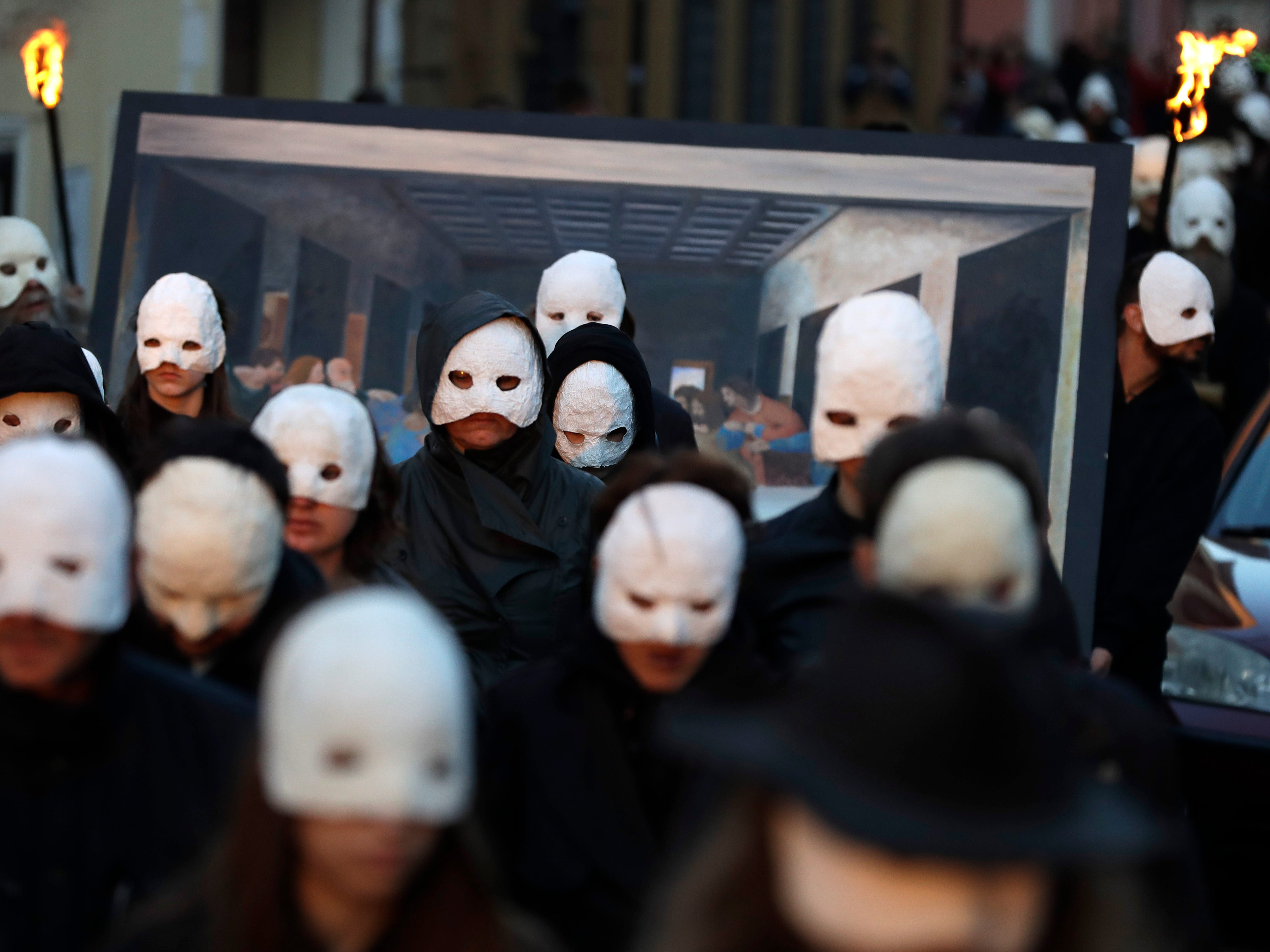 In this picture taken on Thursday, April 18, 2019, participants dressed in black, wearing masks, beating drums and pushing small carts that make a synchronized and loud sound take part in an Easter procession through the streets of Ceske Budejovice, Czech Republic.