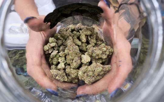 A bud tender displays a jar of cannabis at the High Times 420 SoCal Cannabis Cup in San Bernardino, Calif.