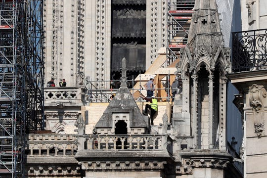 Workers stand by wooden planks supporting Notre Dame cathedral Friday, April 19, 2019 in Paris.