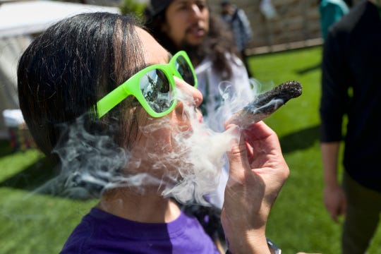 """In this Friday, March 22, 2019 file photo, a participant takes a very smoky puff from a marijuana cigarette during at meet and greet at """"Tommy Chong's Live, Love, and Smoke Tour hosted by GreenTours in the Woodland Hills section of Los Angeles."""