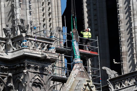 A worker prepares to remove a statue from the damaged Notre Dame cathedral, in Paris, Friday, April 19, 2019.