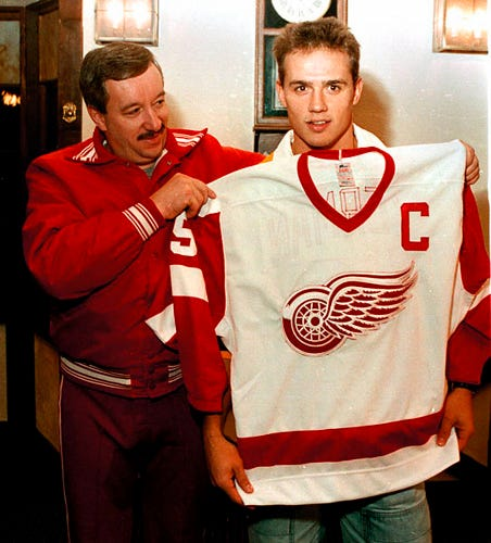 Red Wings coach Jacques Demers gives the Captain's jersey to Steve Yzerman at Oak Park Arena on Oct. 7, 1986.