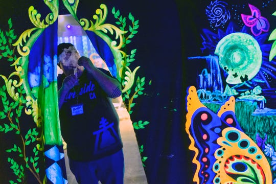 Joshjua Collins from Riverside, Calif. takes a smokes a cannabis concentrate at a lunch break in Zentopia, a 3-d experience during Greentours celebrity 4/20 experience with Tommy Chong in Los Angeles.