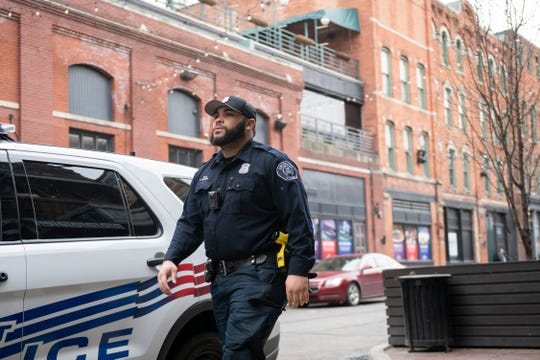 Detroit police officer Austin Hunter keeps an eye on Monroe Street in Greektown on April 18.