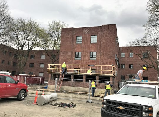 A construction crew works on the exterior of the former Jones Court apartment complex on Baldwin Street in Elmira.