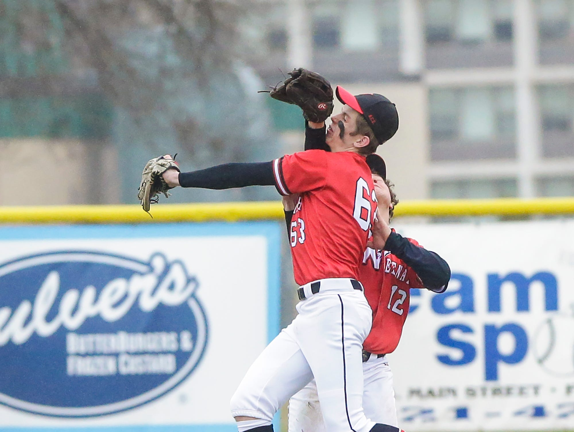 Neenah High School baseball's Samuel Dietrich (63) and Orion Rieden (12) colide after Dietrich made a catch in short centerfield against Fond du Lac High School during their game Thursday, April 18, 2019 in Fond du Lac, Wis. Doug Raflik/USA TODAY NETWORK-Wisconsin