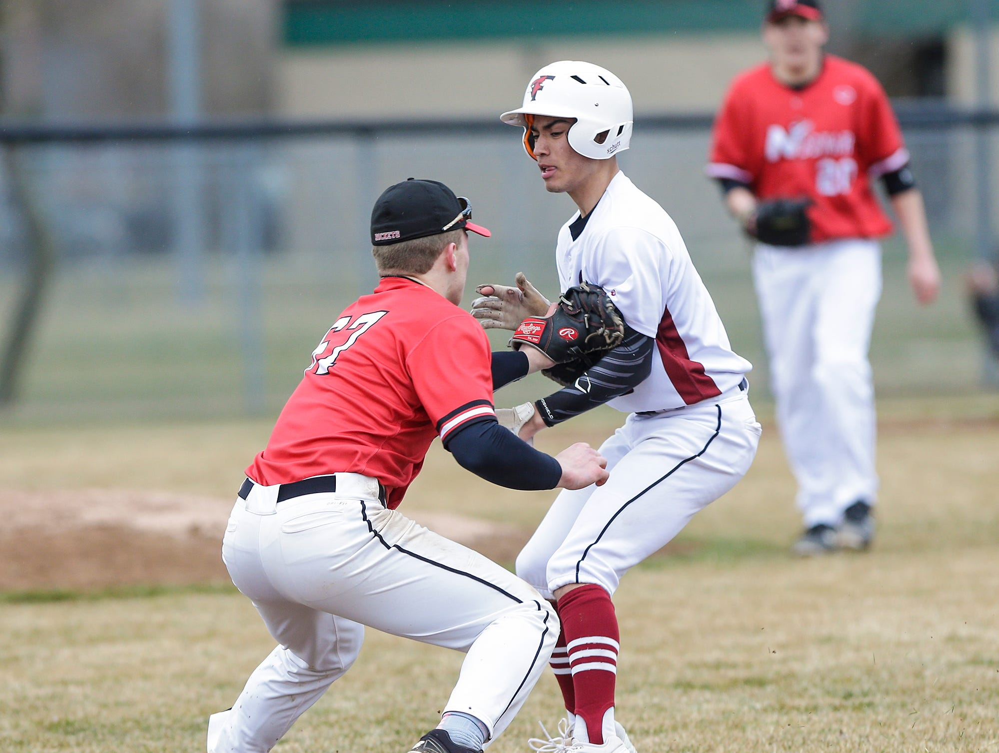 Neenah High School baseball's Logan Eiden picks off Fond du Lac High School's Julian Murillo at first base during their game Thursday, April 18, 2019 in Fond du Lac, Wis. Doug Raflik/USA TODAY NETWORK-Wisconsin