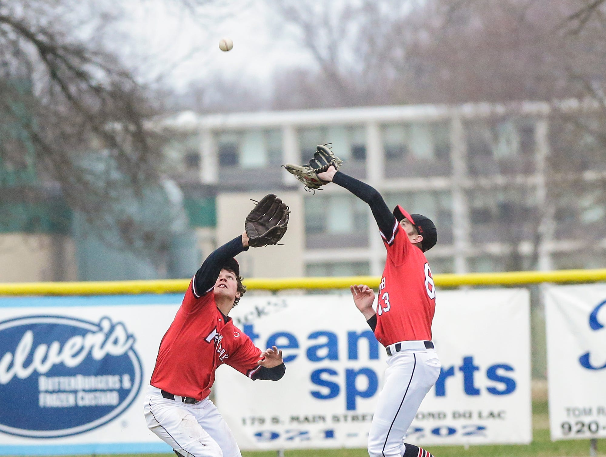 Neenah High School baseball's Samuel Dietrich (63) and Orion Rieden (12) go for a fly ball against Fond du Lac High School during their game Thursday, April 18, 2019 in Fond du Lac, Wis. Doug Raflik/USA TODAY NETWORK-Wisconsin