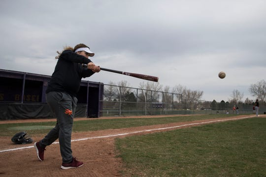 Assistant junior varsity baseball coach Jaelyn Manzanares hits grounders to the infielders during warmup before a game against Fort Collins High School on Tuesday, April 16, 2019, at Fort Collins High School in Fort Collins, Colo.