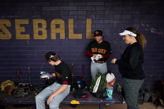 Assistant junior varsity baseball coach Jaelyn Manzanares jokes around with players as they snack in the dugout during a game against Fort Collins High School on Tuesday, April 16, 2019, at Fort Collins High School in Fort Collins, Colo.
