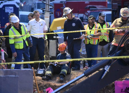 Windsor Severance Fire Rescue Chief Kriz Kazian, in white shirt, and the department's Travis Champan, middle in white fire hat, look into a trench where rescuers tried to save two construction workers Tuesday. The two men died when the 15-foot trench collapsed.