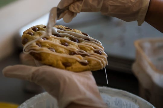 Baker Brooke Buchan drizzles frosting over salted caramel cookies on Thursday, April 18, 2019, at Mary's Mountain Cookies in Fort Collins, Colo.