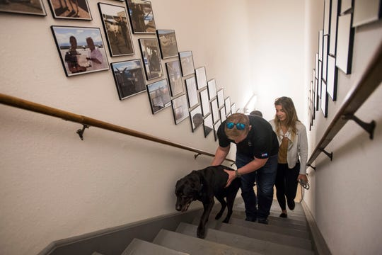 Hangar dog, Duke, a 15-year-old lab, gets help up the stairs from his owner, Carson Chase, who is owner of Leading Edge Flight Training in Loveland, Colo. Following them up the stairs from the hangar to the office is Chase's fiancee, Giovanna Antonelli, on Thursday, April 18, 2019.