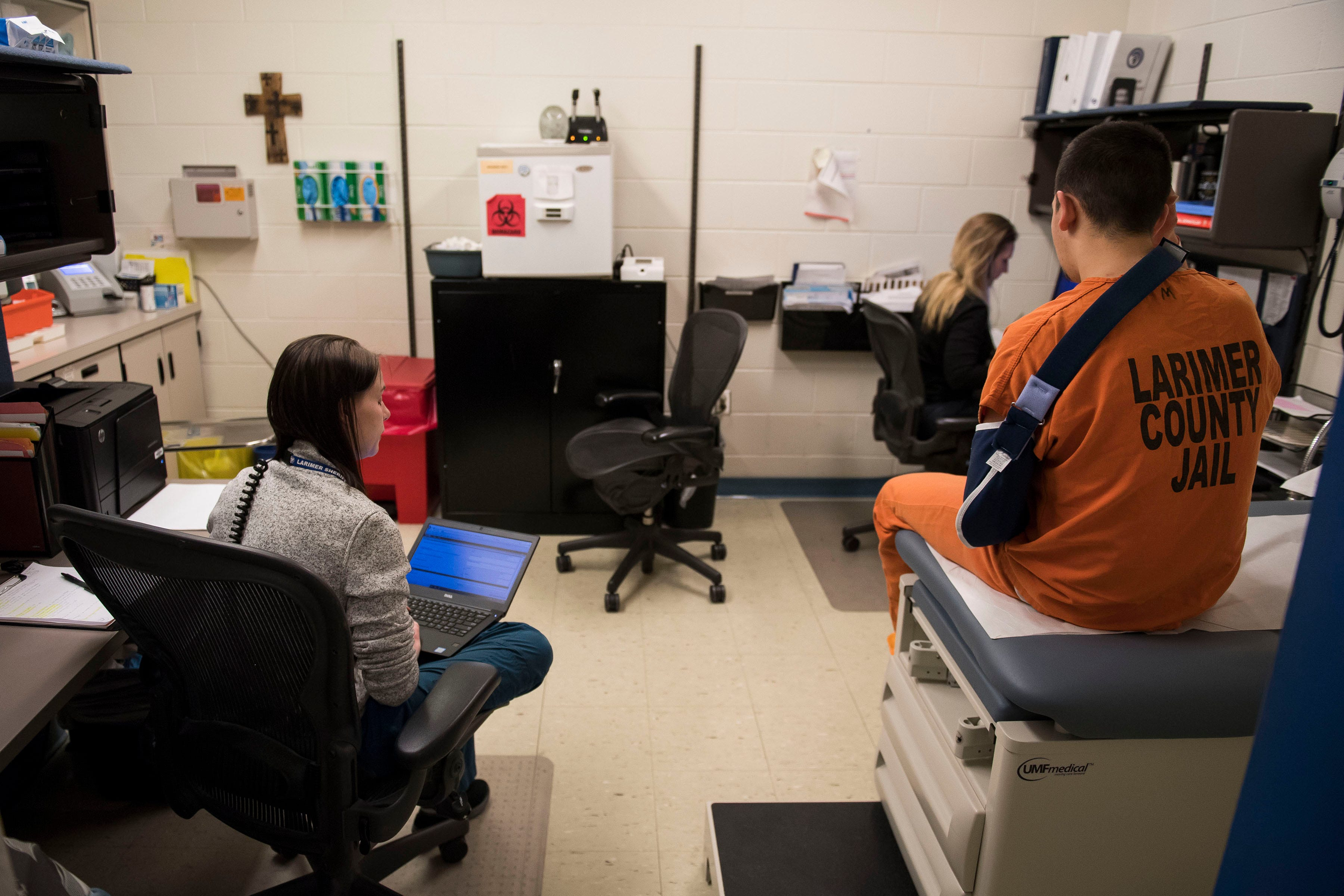 Medical assistant and emergency medical technician Megan Parsons, left, takes notes while she and doctor of nursing practice and certified family nurse practitioner Hannah Holiday talk with an inmate at the Larimer County Jail on Wednesday, April 3, 2019, in Fort Collins, Colo.