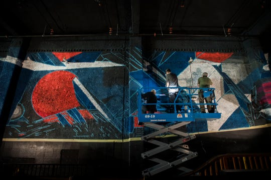 """Artists, from left, Jared Parker, Abram Aleo and Graham """"Oneirogen"""" Hearne work from a scissor lift on Aleo's mural on the South wall of the venue on Friday, April 19, 2019, at The Aggie Theatre in Fort Collins, Colo."""