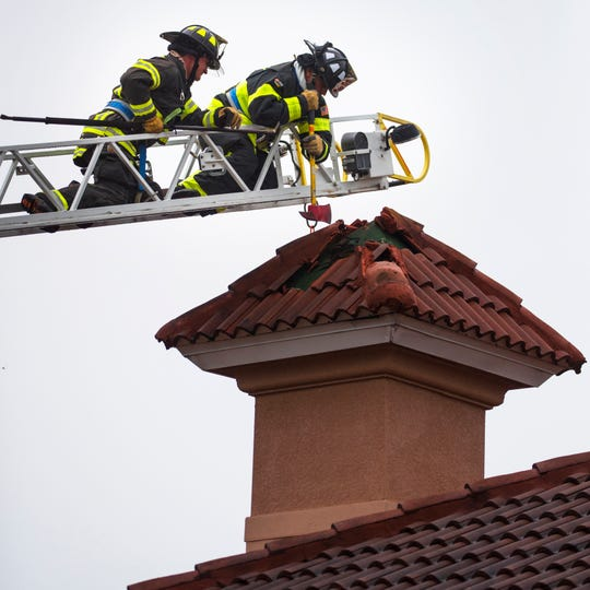 Capt. Ricardo Martinez swings an axe attempting to clear debris from the chimney of an office building in Fort Myers Friday afternoon, April19, 2019. The roof was struck by lightning causing a fire. Employees were evacuated, but no one was injured.