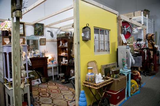 Sally VanDuzer-Fulton's booth, 'The Boom Boom Room,' features a handmade wooden desk from the 1920s, an end table painted violet and gold, a music cabinet for sheet music, her father's cameras on display in a glass cabinet, old books, a fireplace mantle, antique crockery, vintage suitcases and a pair of golf shoes.
