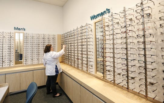 Katie Kotsonis puts a pair of glasses on a display rack at the Shopko Optical store in Oshkosh.