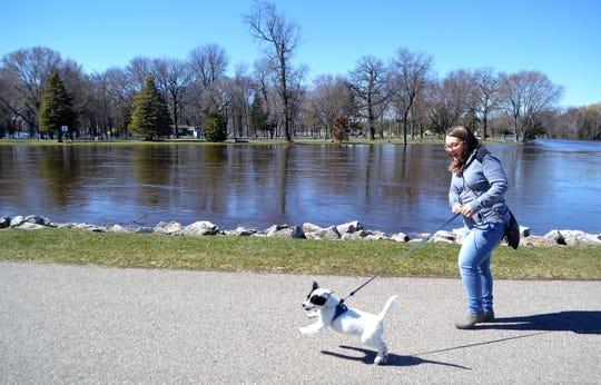 Faith Treat walks her dog, Lena, next to the flooded Oconto River on Friday morning. The river has flooded Holtwood Park and Campground in the background.