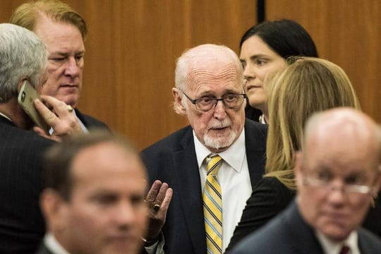 Former SC Rep Rick Quinn looks on as his father, political consultant Richard Quinn, talks with lawyers following a hearing in their corruption cases. Should their clients and other legislators also be prosecuted?