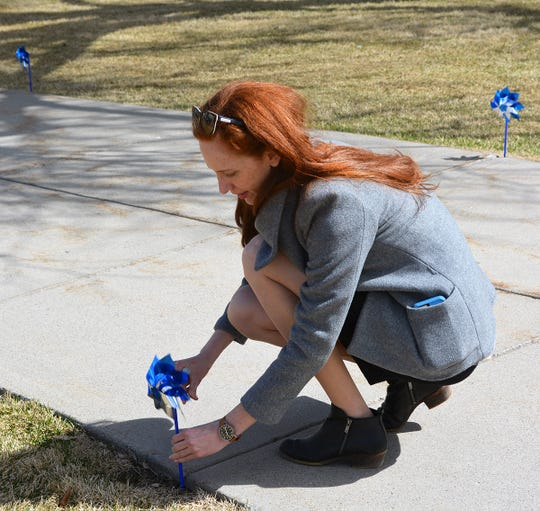 Laura Smith, deputy director of the Department of Public Health and Human Services, plants a pinwheel Wednesday at the state Capitol where attendees of the Prevent Child Abuse and Neglect Conference helped plant about 1,500 pinwheels. Pinwheels for Prevention is a national public awareness campaign to convey the message that every child deserves a chance to be raised in a healthy, safe and nurturing environment.