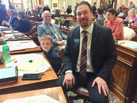 Rep. Joshua Kassmier, R-Fort Benton, and son, Banks, 6, on the House floor Thursday.