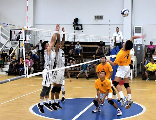 George Washington High's senior outside hitter Koby Pocaigue reaches high to hit past the Saint Paul block in an IIAAG Boys Volleyball match April 18 at Saint Paul.