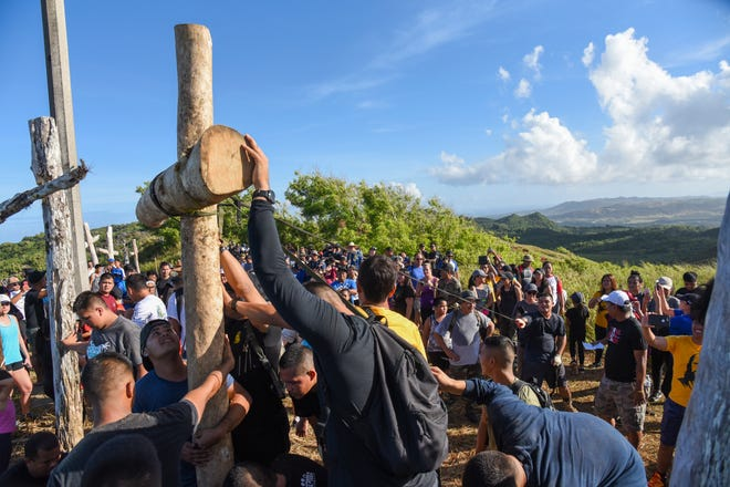 Crossbearers work together to install a new cross on Mount Jumullong Manglo during the annual Good Friday Hike in this April 19 file photo.