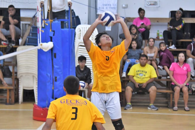 George Washington High's Francis Montejo sets his opposite hitter on April 18 in an IIAAG Boys Volleyball match against Saint Paul at the Warriors' gym.