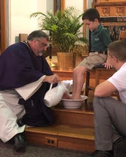 "Just as Jesus did with his disciples, Father Larry McBride washes the feet of student Eastin Fulkerson as Holy Name School Principal Scottie Koonce looks on. ""This reminds us of our calling to be a servant and friend to those around us,"" wrote Holy Name School's Emma Bridges in an email to The Gleaner. The same was done with a teacher from the school. This ceremony was part of Wednesday's Holy Week Mass for students and faculty at Holy Name Catholic School."